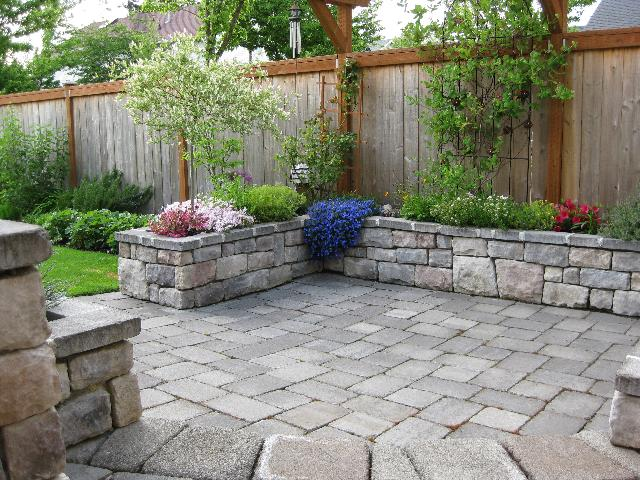 nice-patio-area-with-garden-andnice-wood-wall-on-the-border-and-lifted-flowers-on-stone-wall